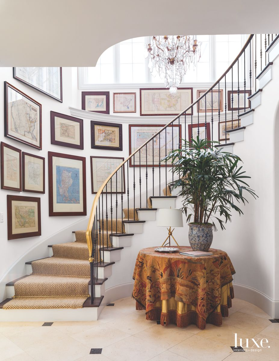 Winding Staircase Lined with Framed Maps in Dramatic Dallas Home