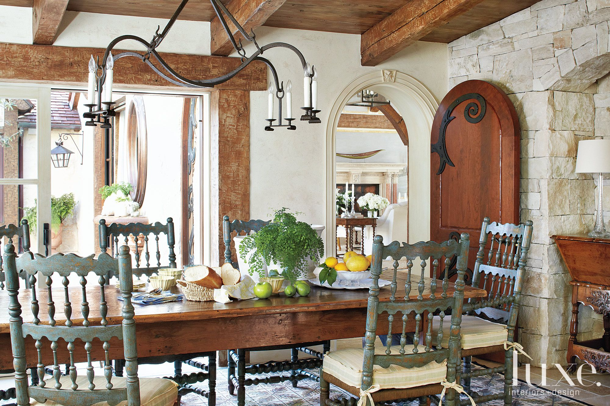 Mediterranean Cream Dining Room with Stone Accent Wall