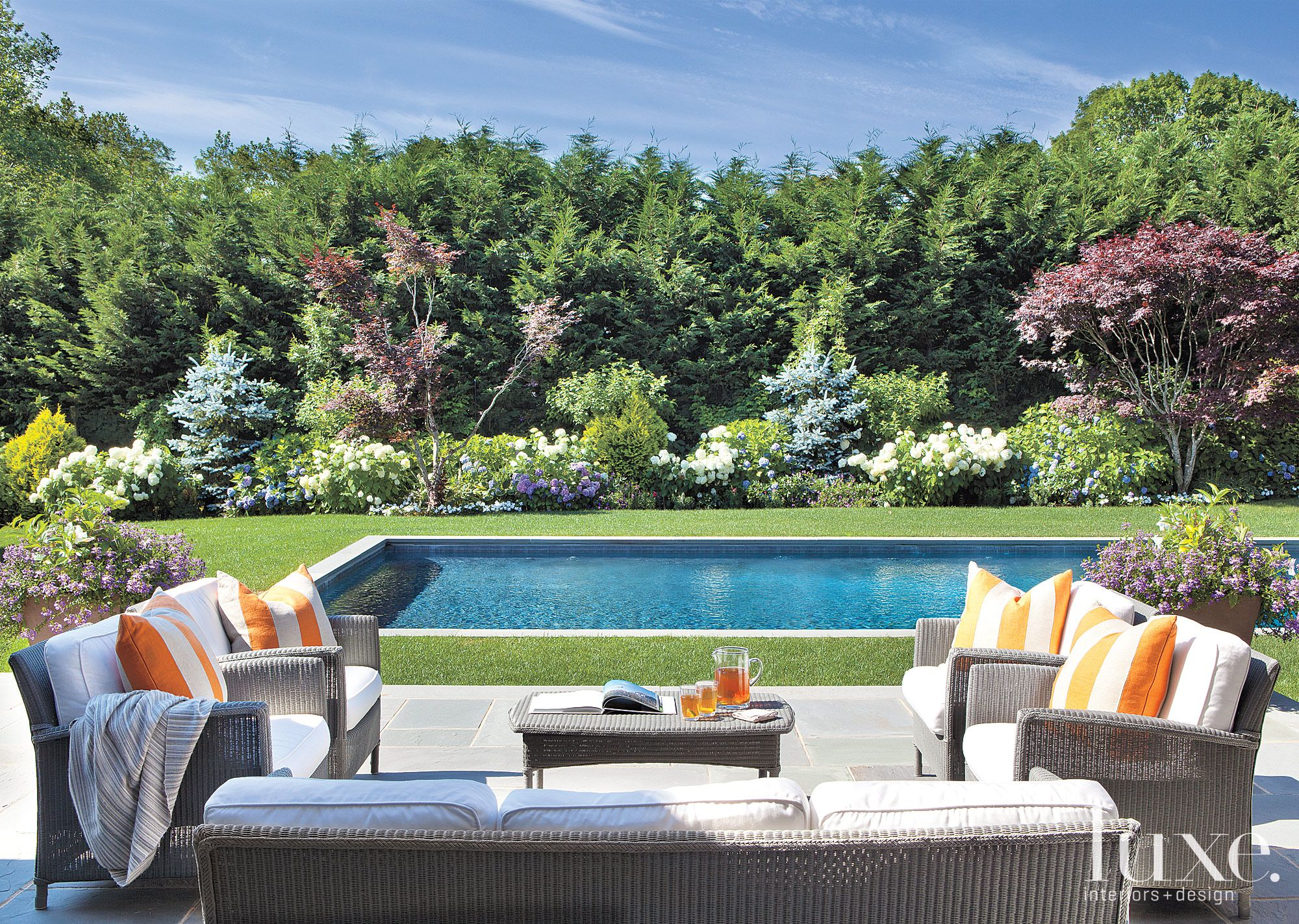 Traditional Neutral Pool Area with Lush Gardens