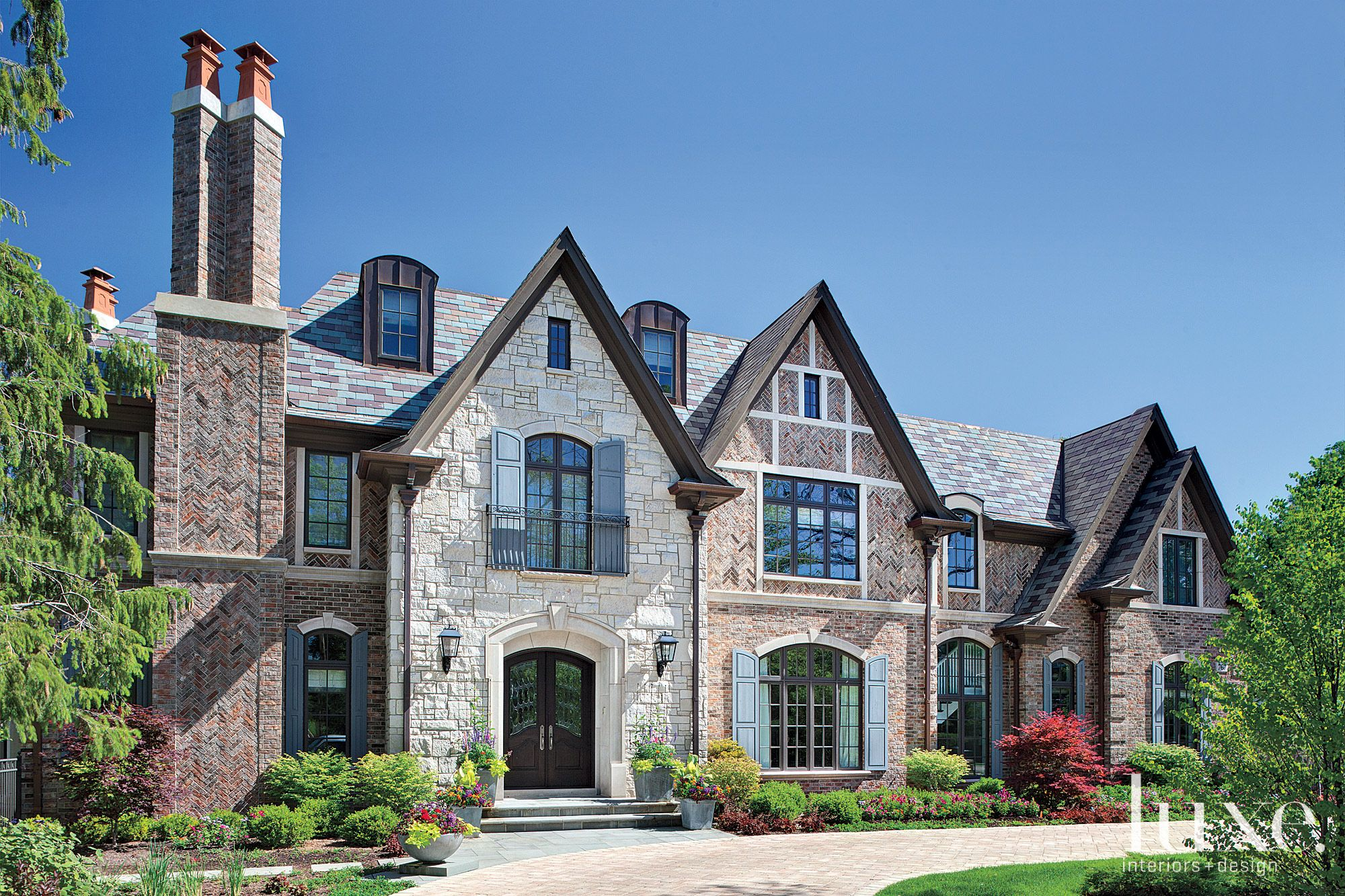 Contemporary Stone Tudor Facade with Potted Plants