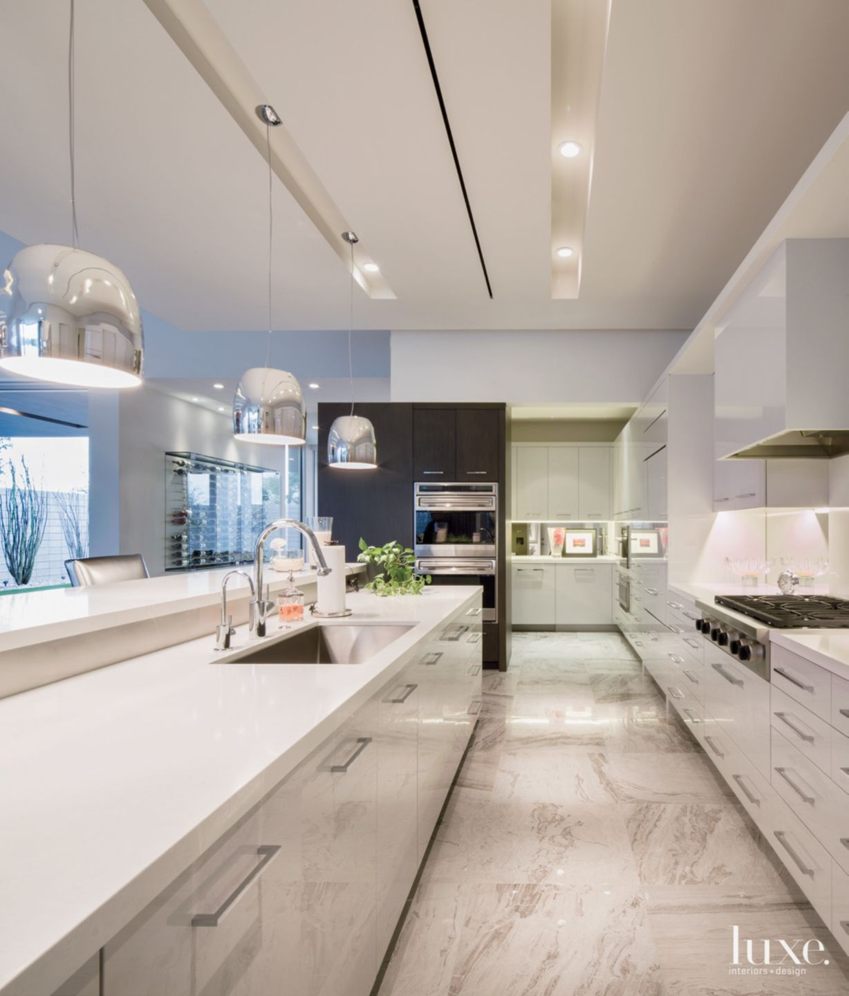Modern White Kitchen with Hanging Chrome Pendants
