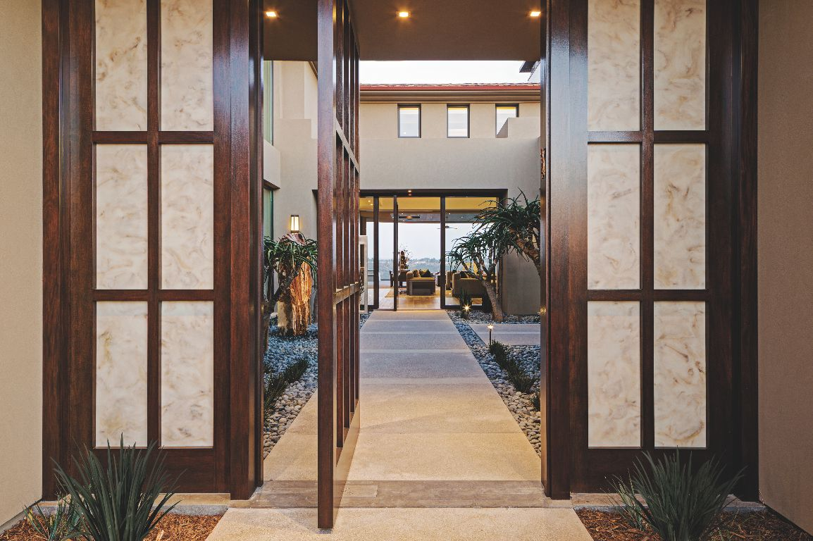 Pivoting Contemporary Wooden Front Door Leading Into a Courtyard