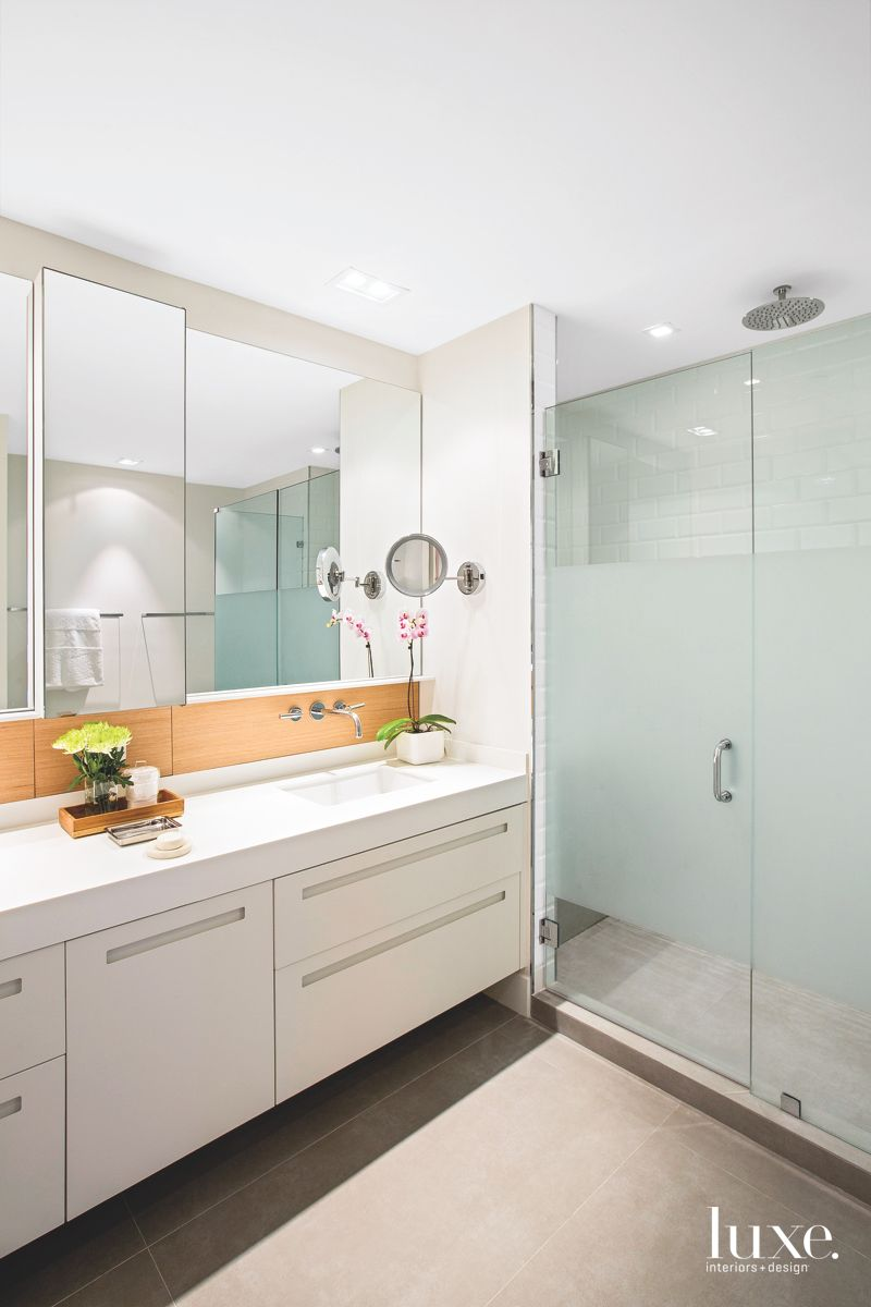 Sleek White and Glass Master Bathroom with Flowers