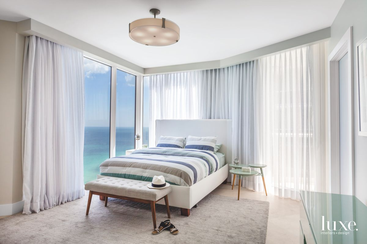 Soft Blue Guest Bedroom with Ocean Views and Plush Gray Carpet