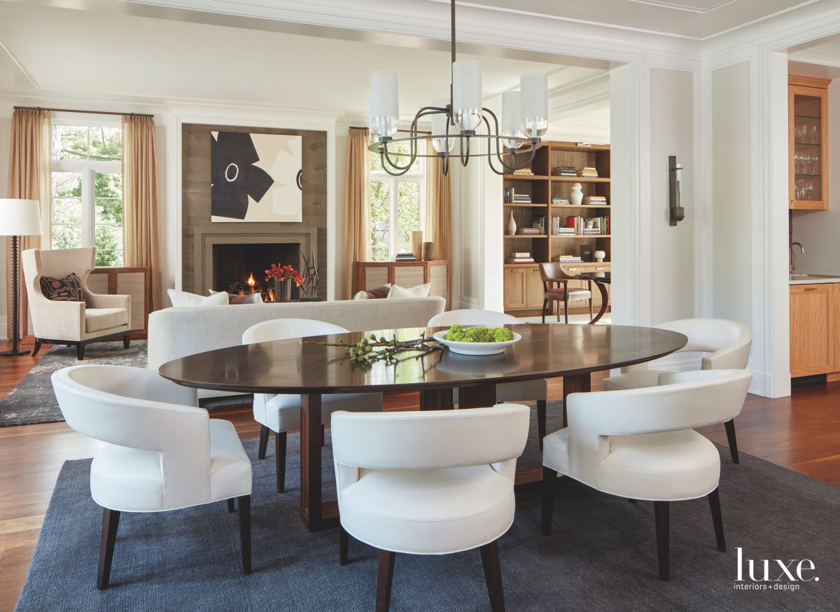 Rounded Soft Dining Room with Chandelier and White Chairs