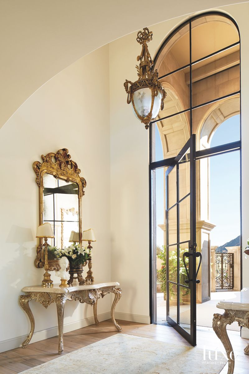 High Ceiling Entryway with Arched Glass Door and Mirror