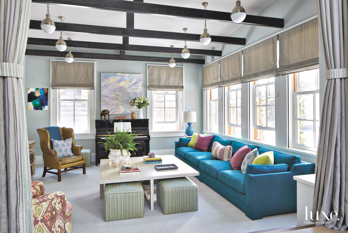 Blue Sofa, Wing Chair, and Ottoman Living Room with Beam Ceiling