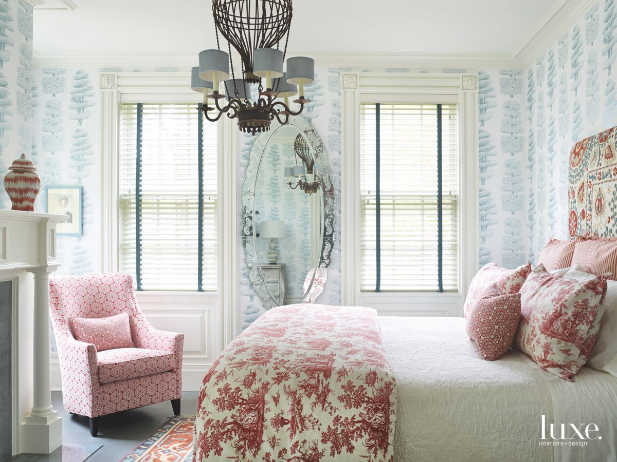 Blue and Pink Patterned Fabric and Wallpaper Guest Bedroom with Chair and Chandelier