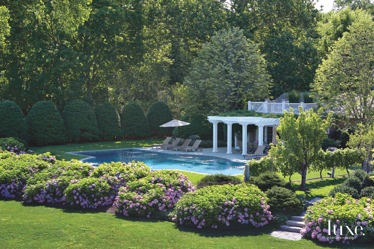 Pool Exterior Home Shot with Flower Bushes and Four Lounge Chairs
