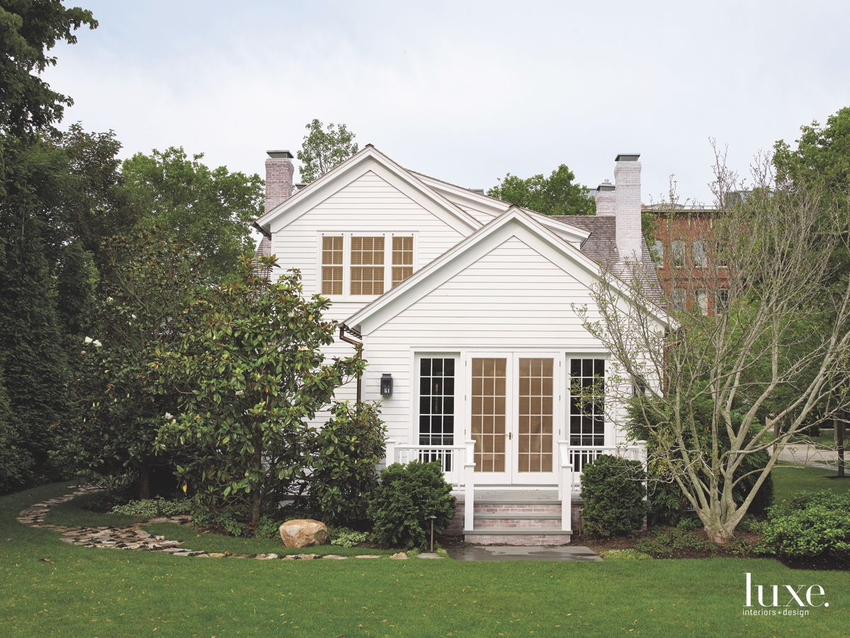 White Siding Guest House with Landscaping and Green Lawn