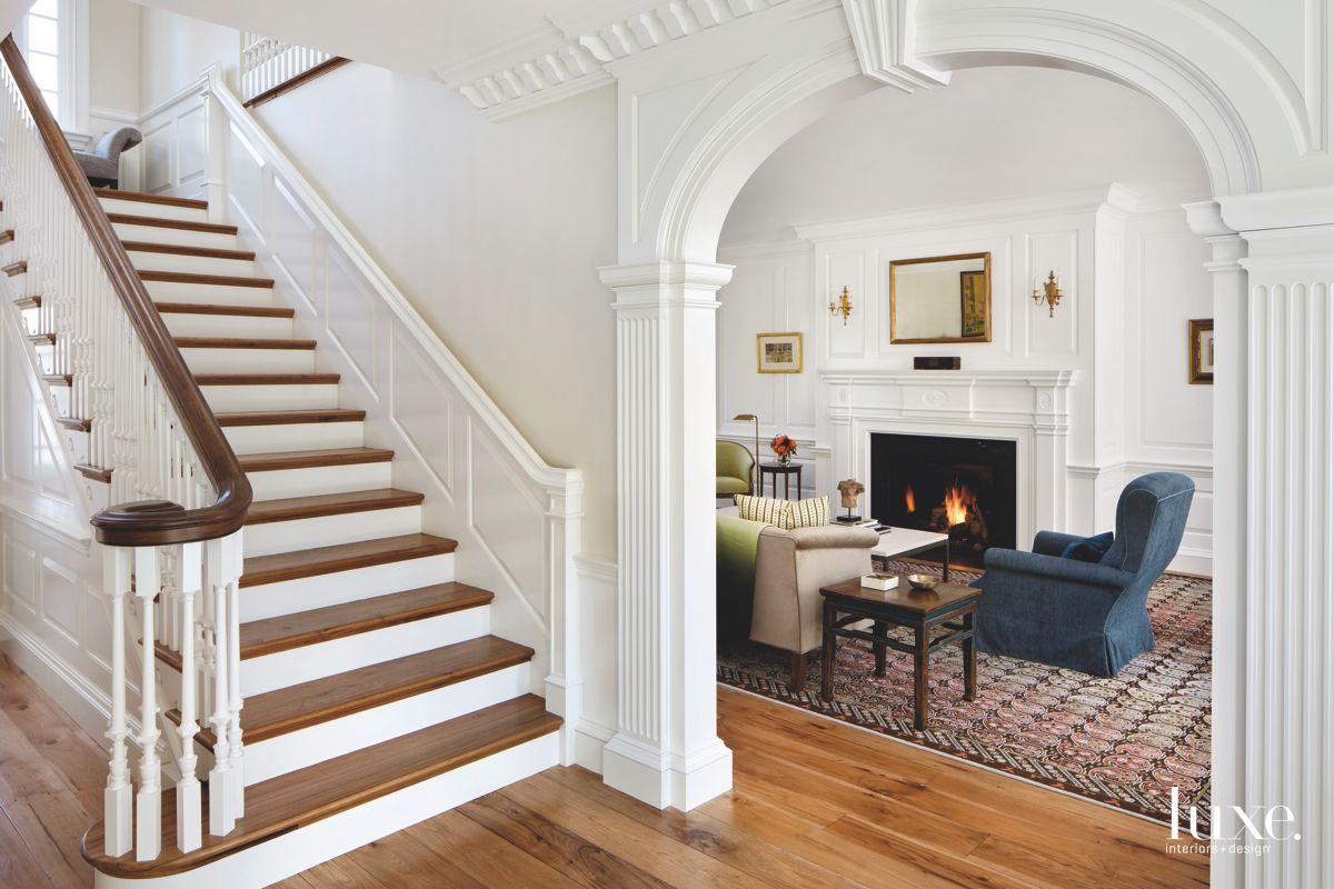 Wooden Traditional Staircase with White Crown Moulding Arch Entrance and Fireplace
