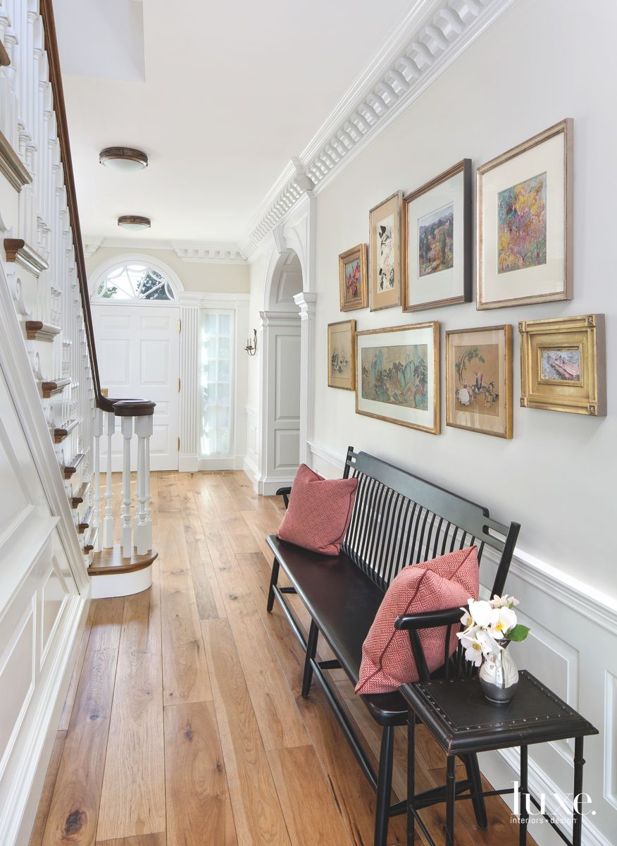 Ornate Crown Moulding Hallway with Framed Artwork and Bench