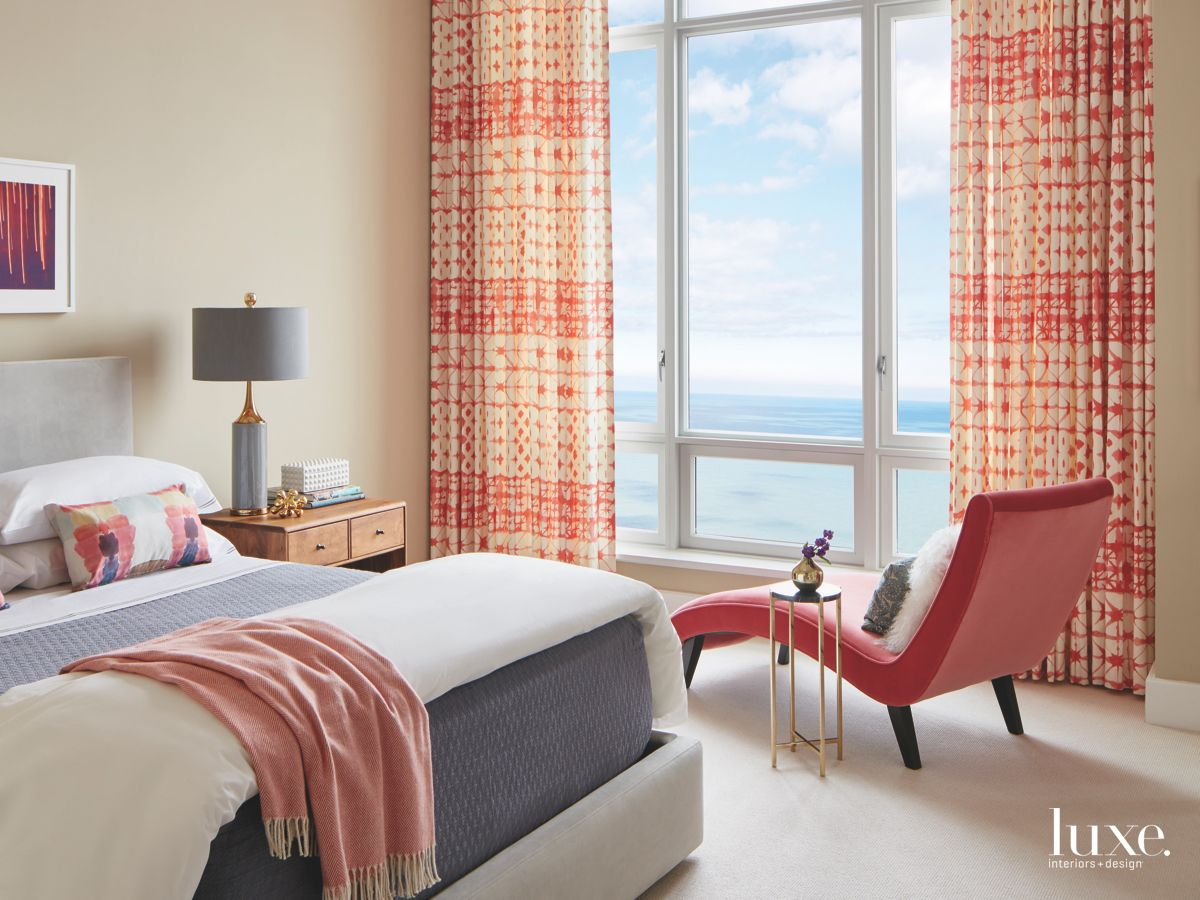 Red Chaise Lounge Chair Bedroom with Water View and Brightly Colored Curtains