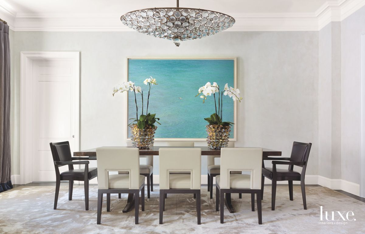 Blue Photograph-Accented Dining Room Wall with Chandelier and Orchids