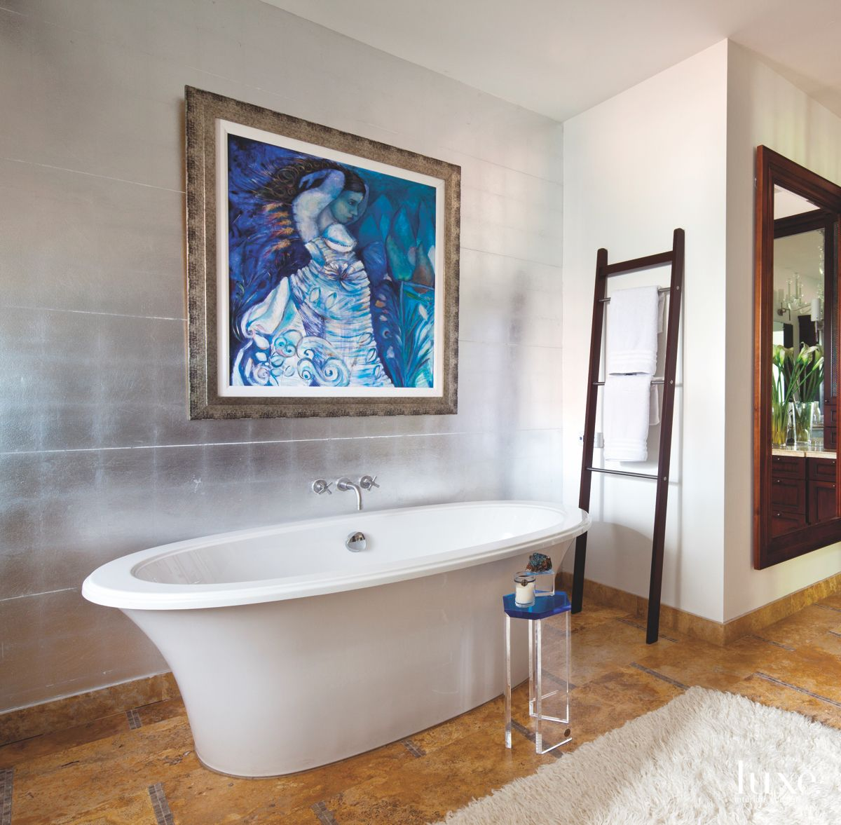 Moody Blue Artwork Master Bathroom with Large Soaking Tub, Lucite Side Table