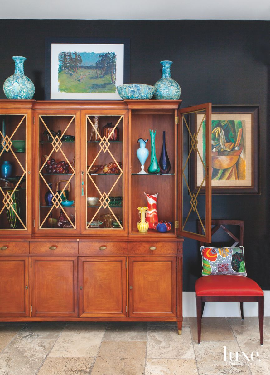 Colorful Glass Cabinet Storage with Black Wall and Side Chair