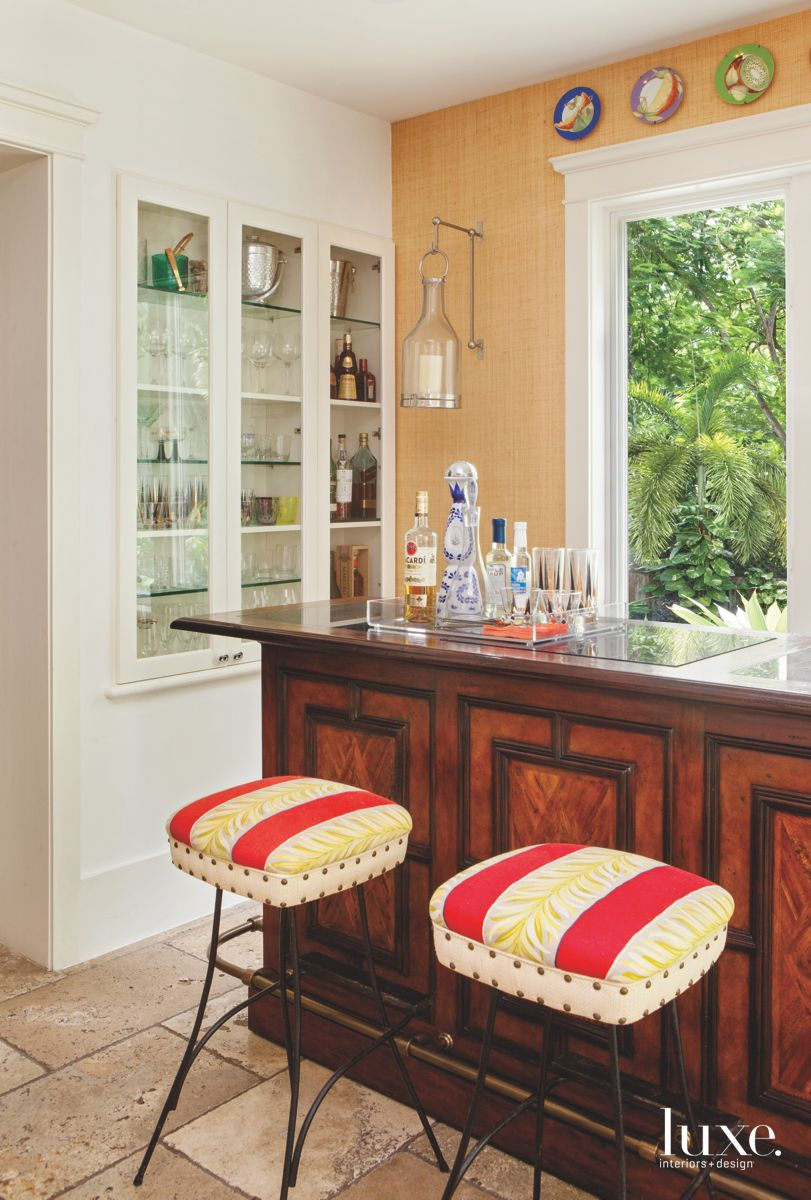Red and Yellow Patterned Bar Stools with Dark Wood Bar and Liquor Cabinet