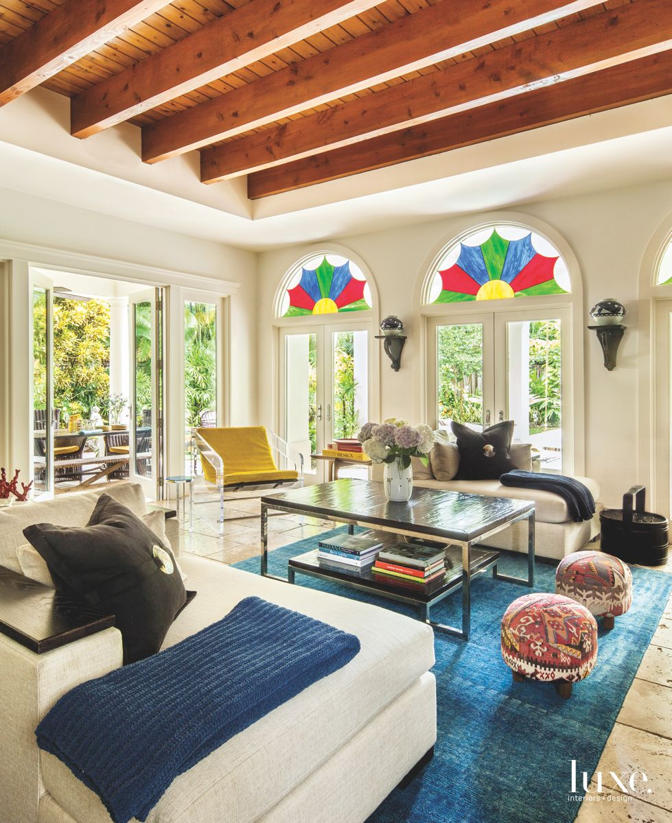 Stained Geometric Glass Arched Window Living Room with Lucite Chair and Ottomans