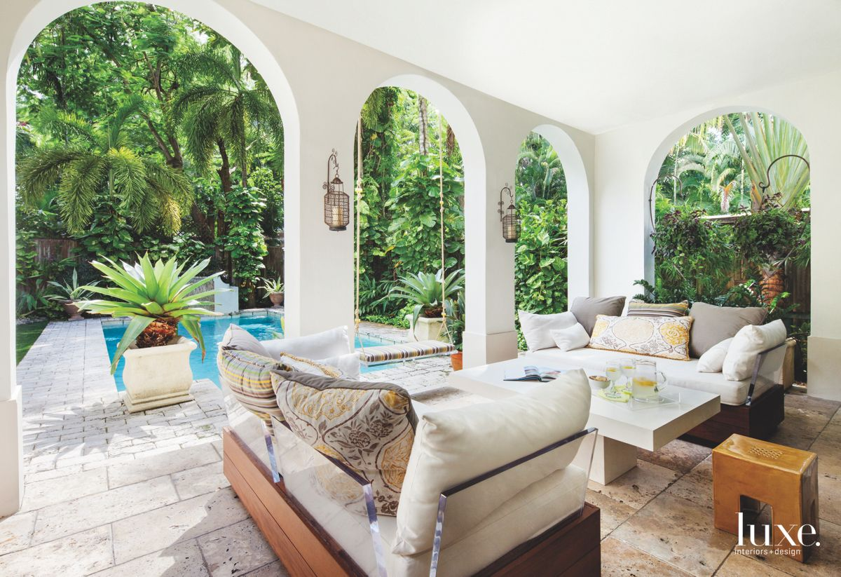 White Arched Loggia with Pool Adjacent and Glass Outdoor Seating
