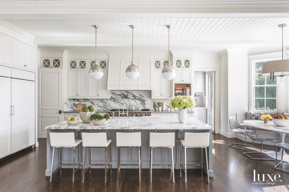 Marble Backsplash Kitchen with White Cabinetry and Spherical Pendant Lighting with Island Barstools