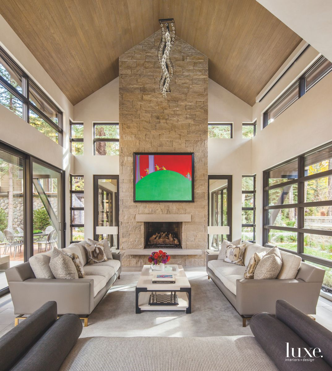 High Vaulted Ceiling Living Room with Stone Fireplace and Dangling Artwork