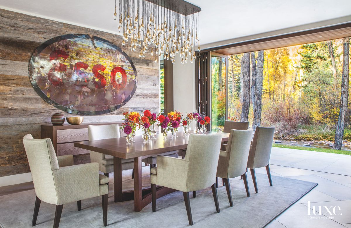 Wooden Wall Dining Room with Dangling Chandelier and Flower Arrangements