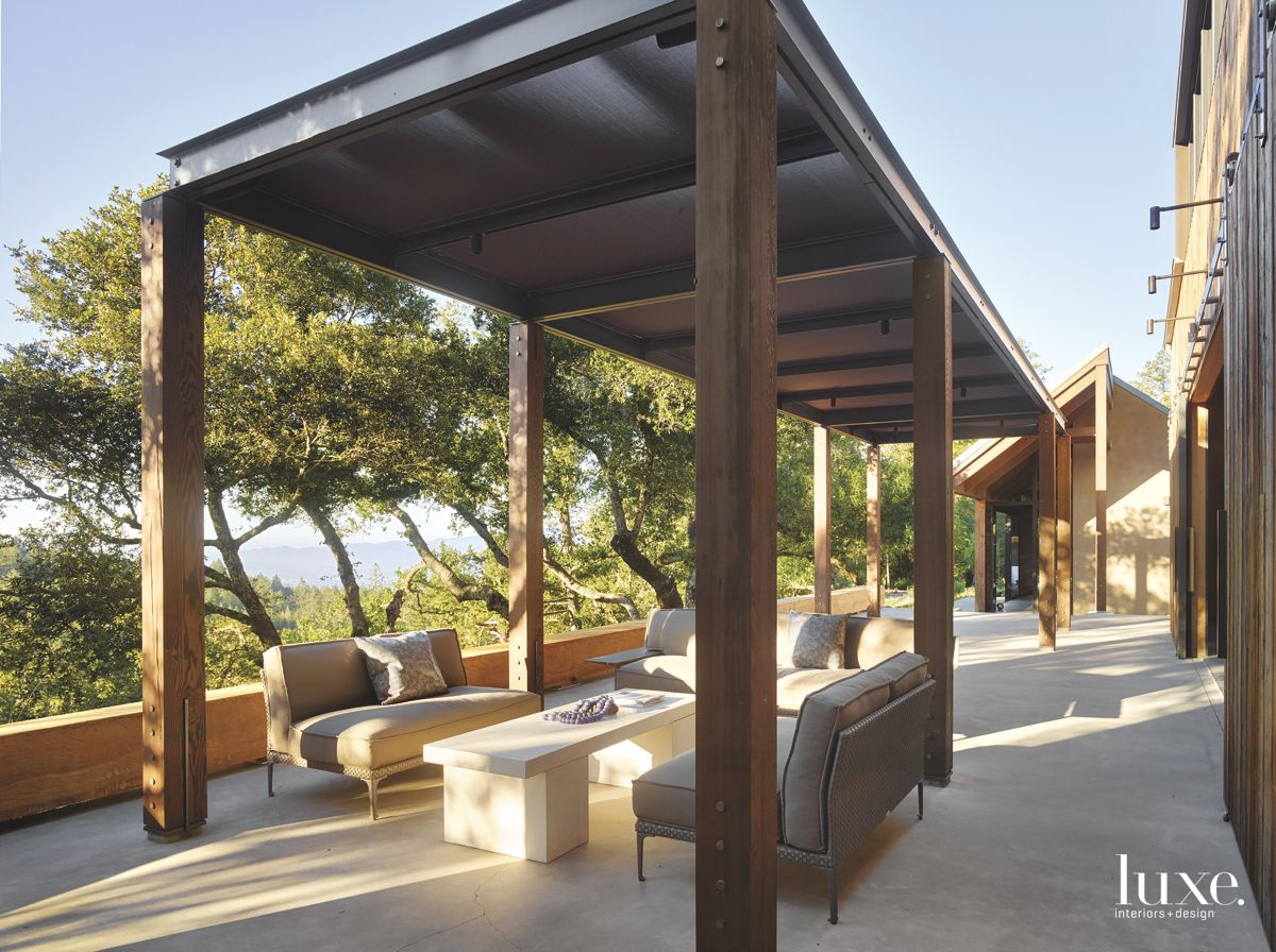 Industrial Covered Patio with Tree Views and Outdoor Furniture
