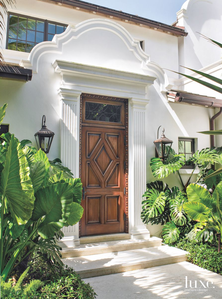 Traditional White Front Door Entryway with Lush Plantings Surround