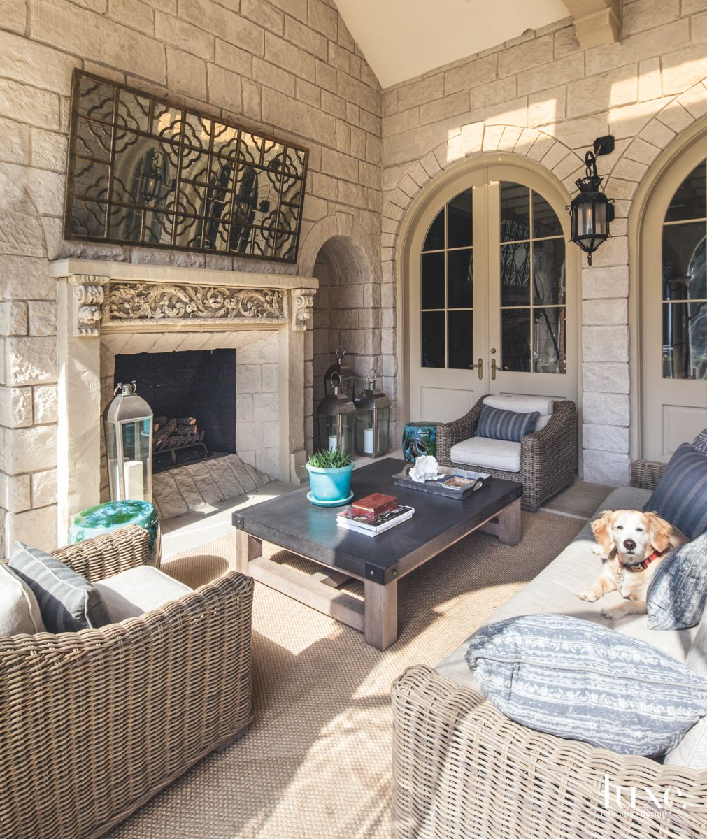 Wicker Outdoor Seating Area with Fireplace and Dog