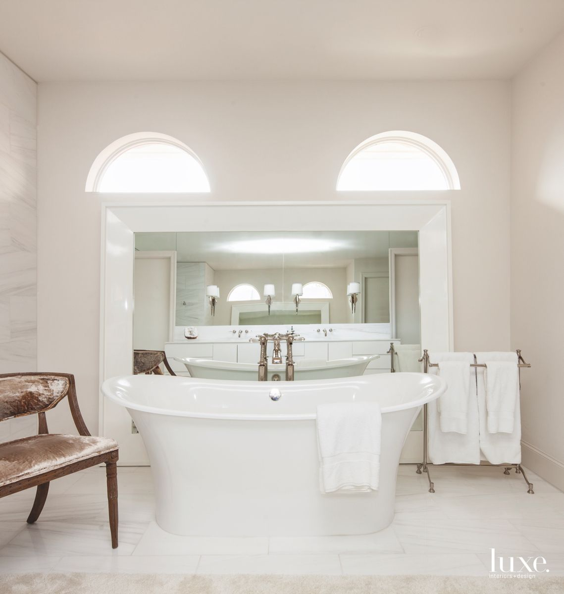 All-White Master Bathroom with Large Freestanding Tub and Arc Windows
