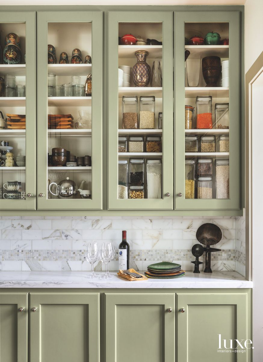 Kitchen Filled with a Warm Green Hue and Marble Backsplash
