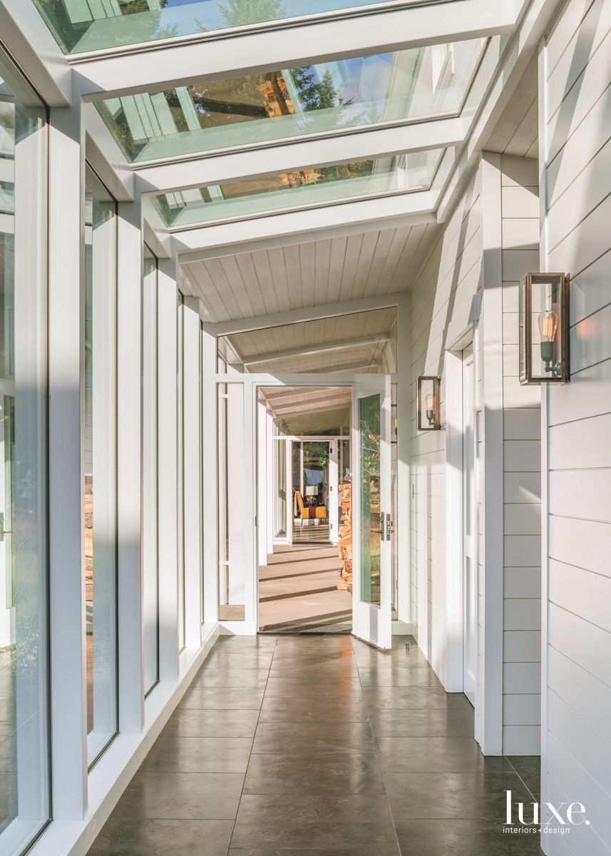 Glass and Light Filled Hallway with Sconces and Skylights