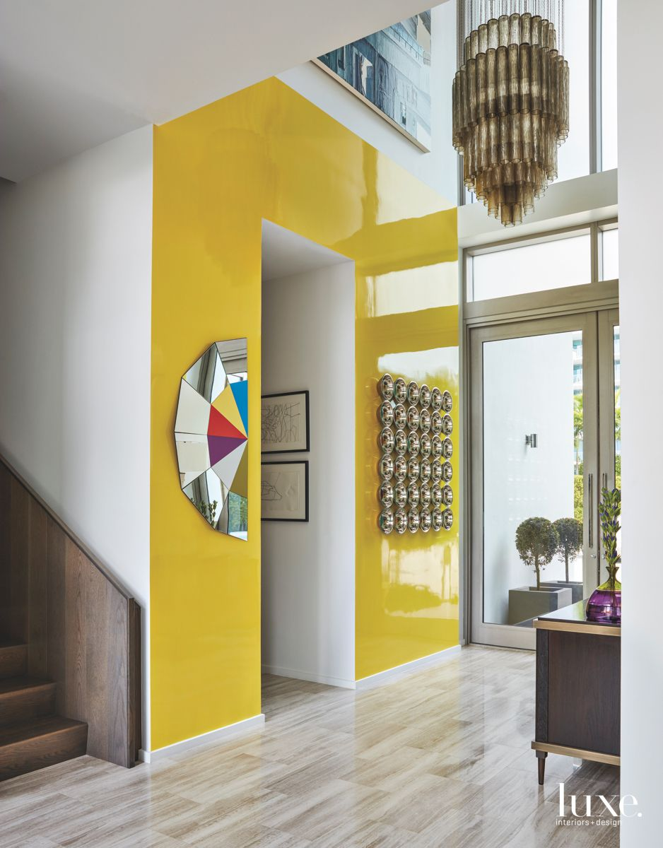 Bold Yellow Lacquer Wall Entry with Chandelier and Artwork