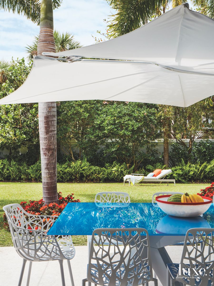 Bright Blue Outdoor Dining Table with Umbrella and Palm Tree