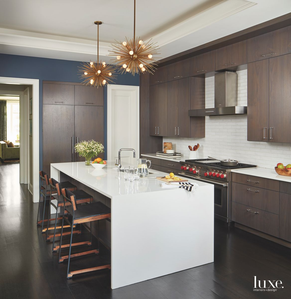 Brown Cabinet Kitchen with Starburst Pendant Lighting and Barstools