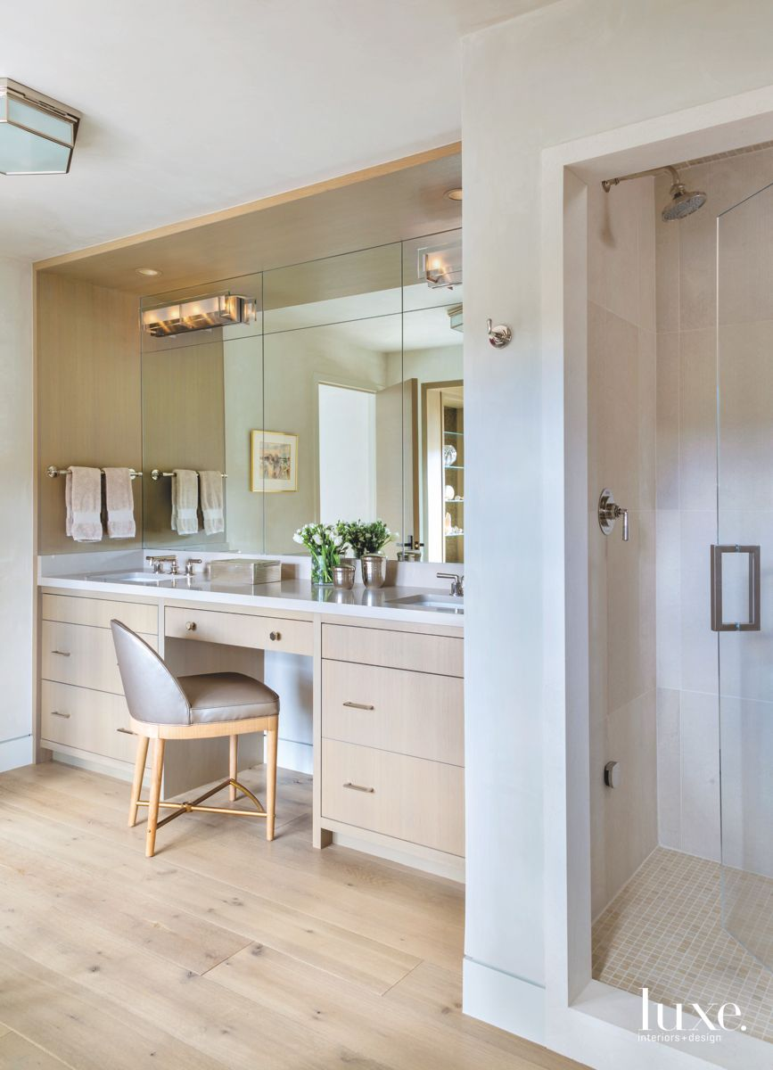 Mirror Vanity Bathroom with Neutral Gray Chair and Neutral Cabinetry