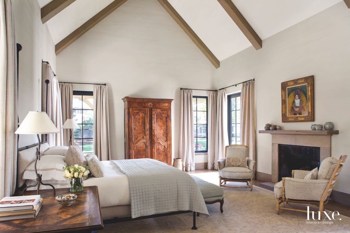 Vaulted Wood Beam Ceiling Master Bedroom with Fireplace and Artwork and Wood Armoir