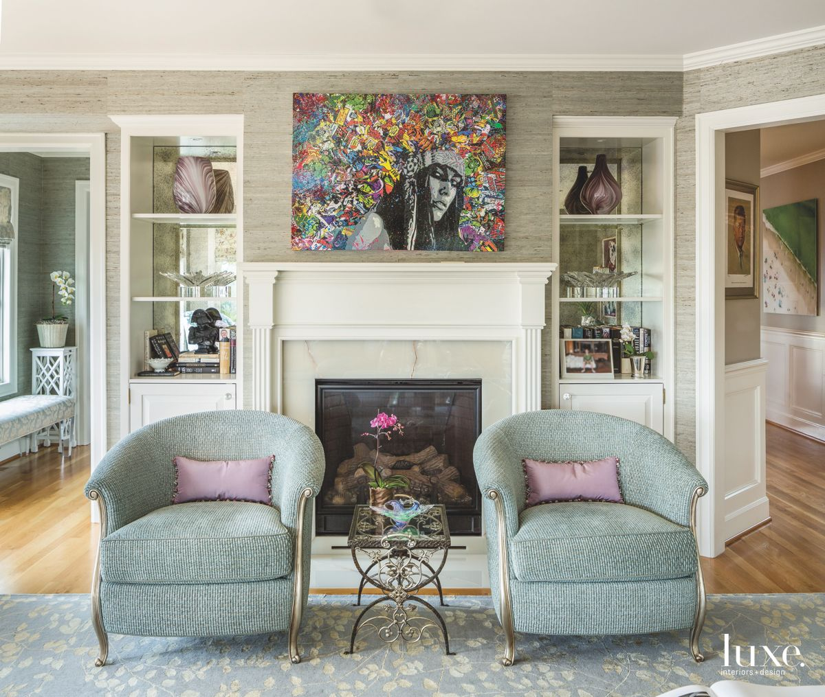 Twin Teal Chair Living Room with Colorful Art and Fireplace