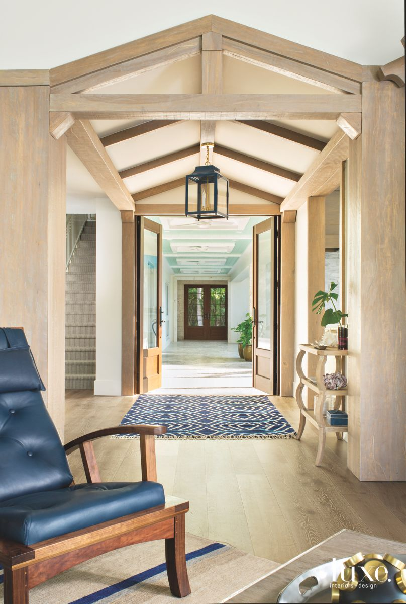 Natural Wooden Entryway with Deep Blue Rug  and Leather Chair