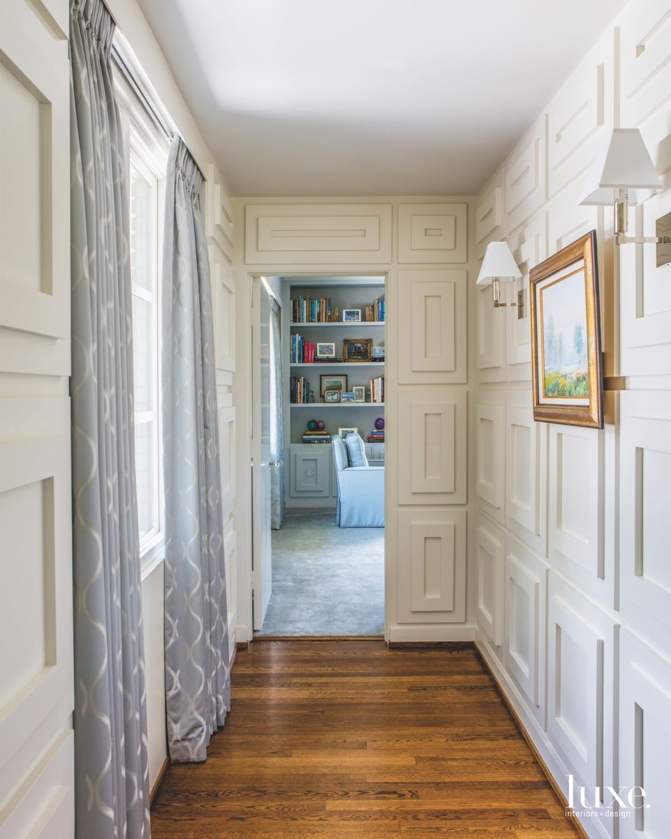 Rectangular White Wood Paneling Hallway with Framed Artwork and Window Curtains