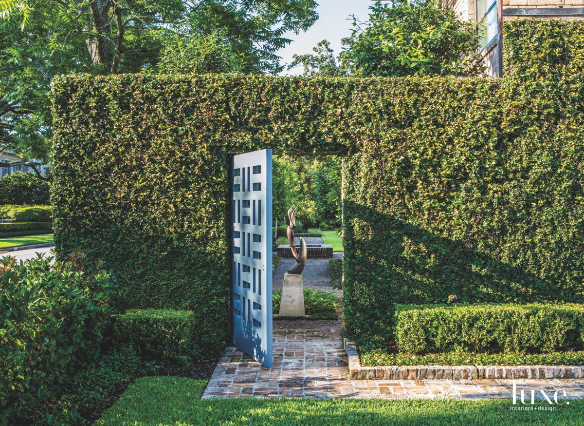 Garden Slot Door with Sculpture View Brick Walkway and Hedges