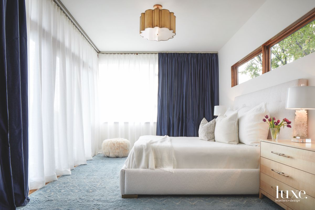 Billowy White Master Bedroom Curtain Surround with Fluffy Ottoman and Clerestory Windows