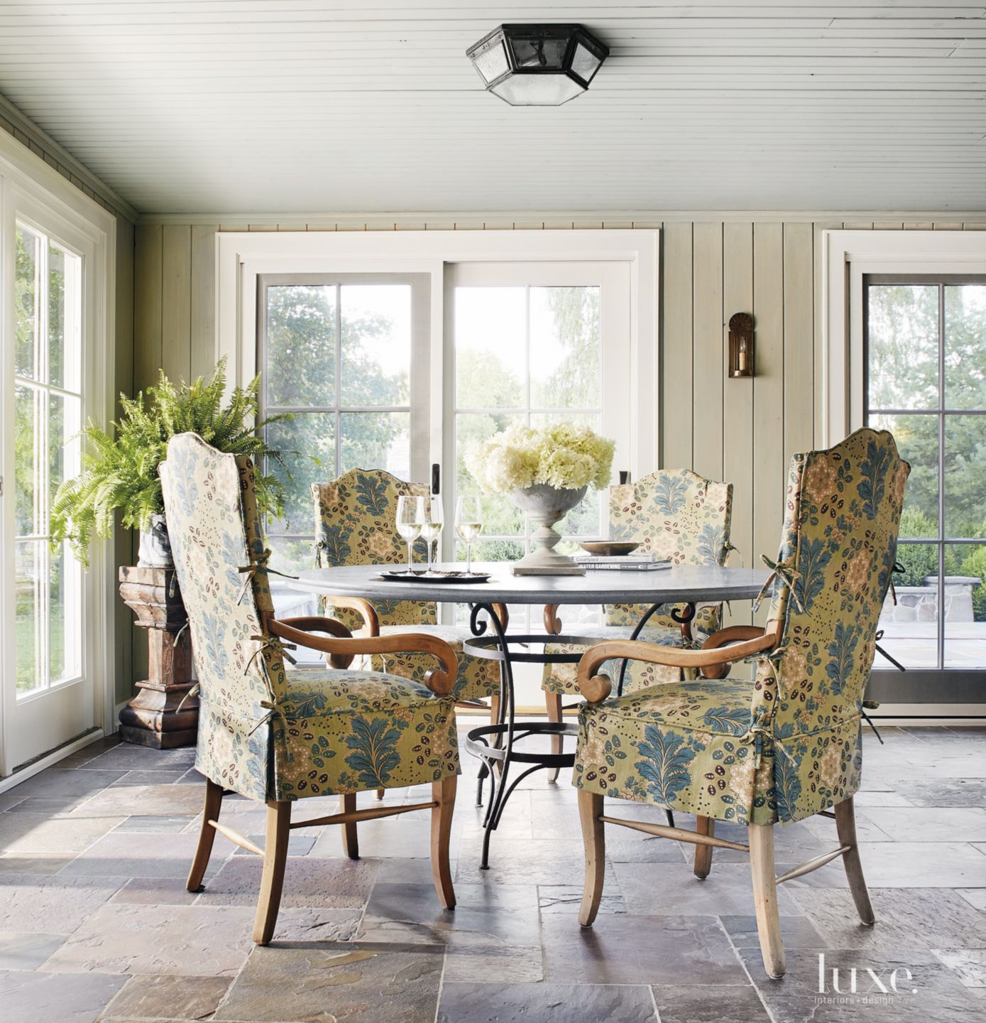 Transitional Neutral Sunroom with Iron Table