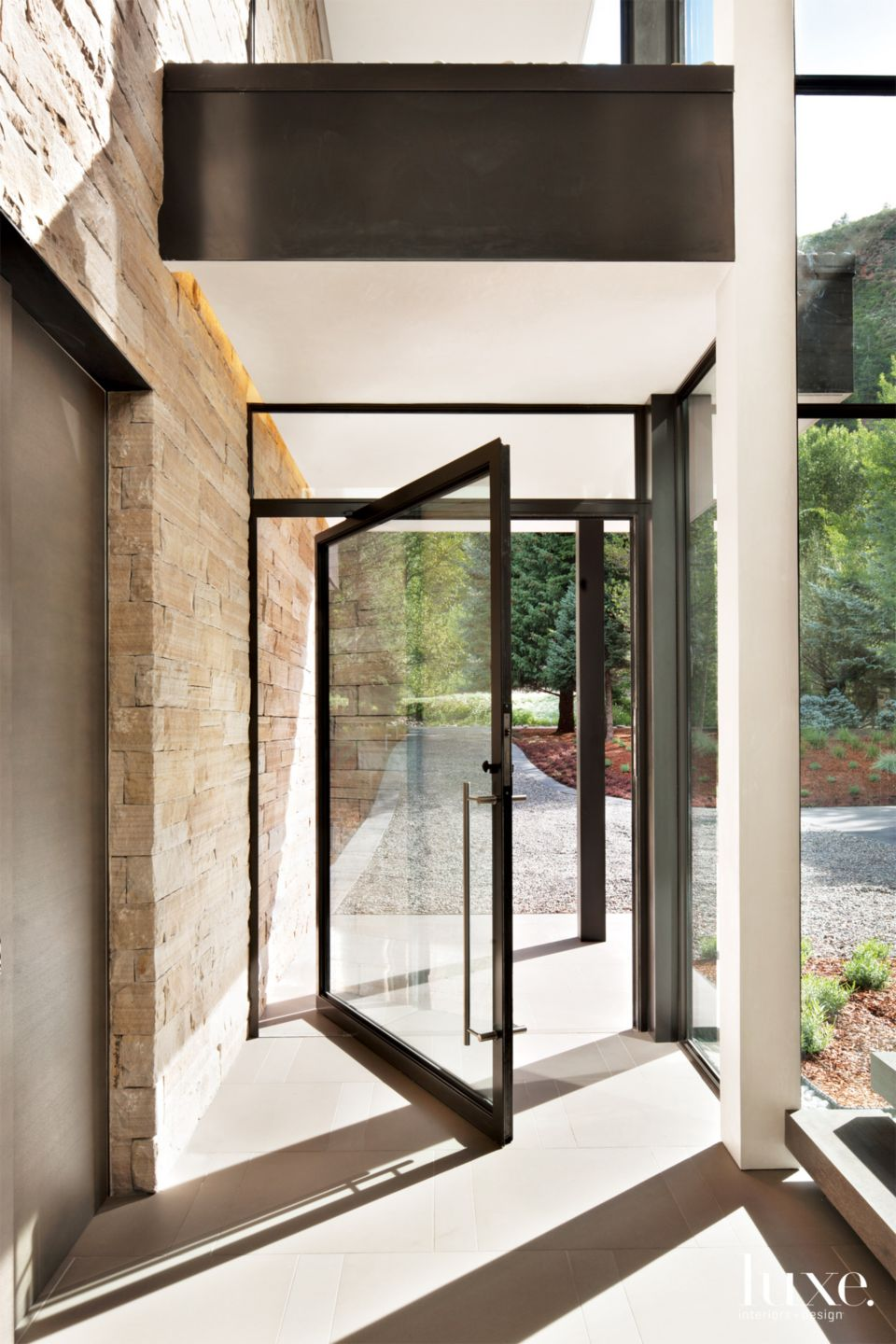 Contemporary Neutral Entry with Steel-and-Glass Pivot Door