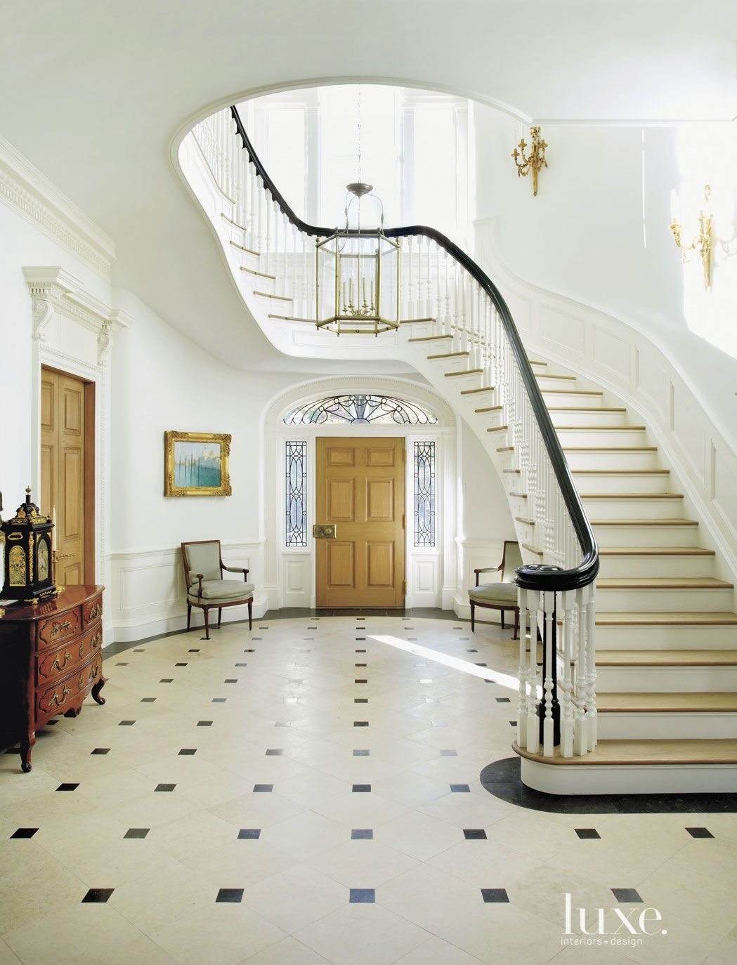 Traditional White Entry with Curved Staircase