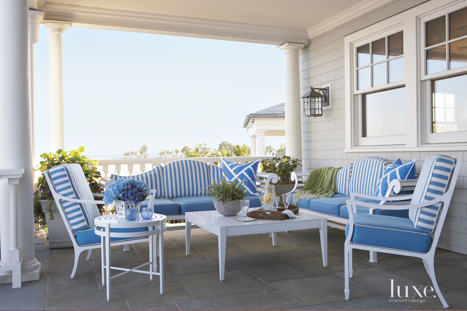 Traditional White Outdoor Seating Area with Striped Cushions