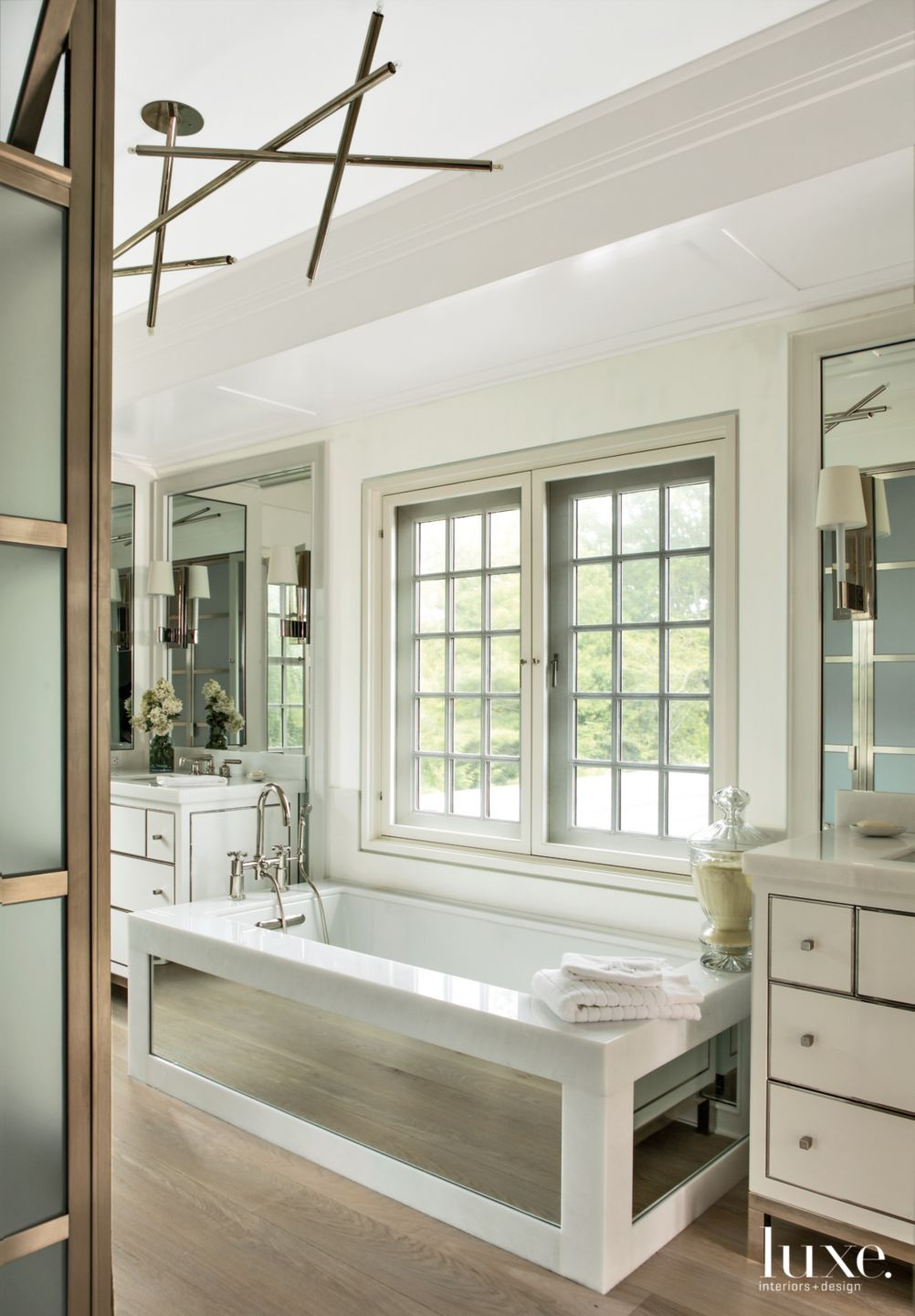 Modern White Master Bathroom with Mirror-Paneled Tub