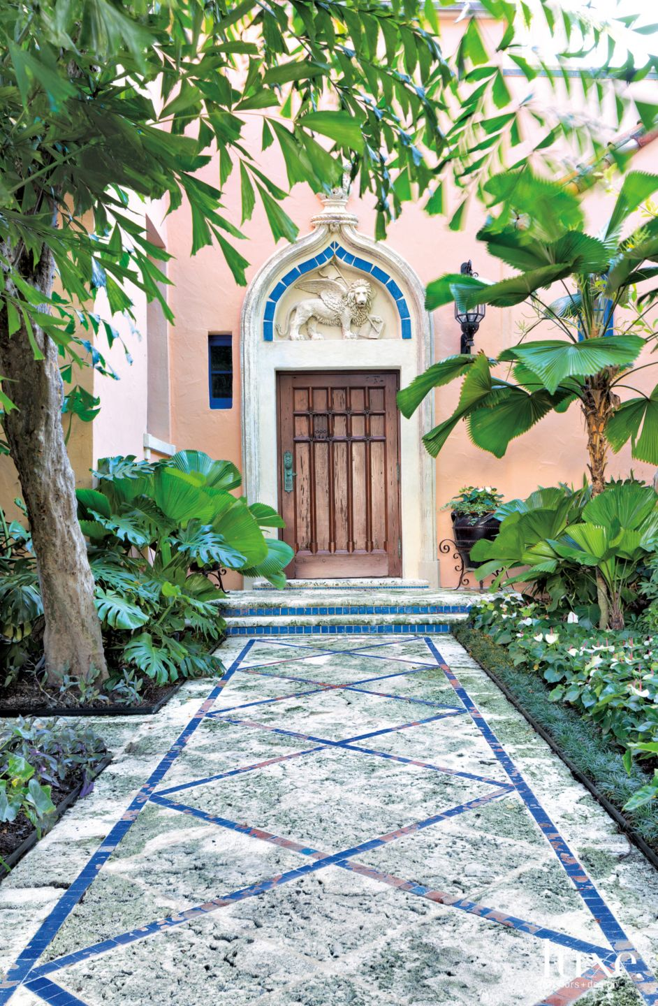 Mediterranean Pink Exterior Entry with Lush Greenery