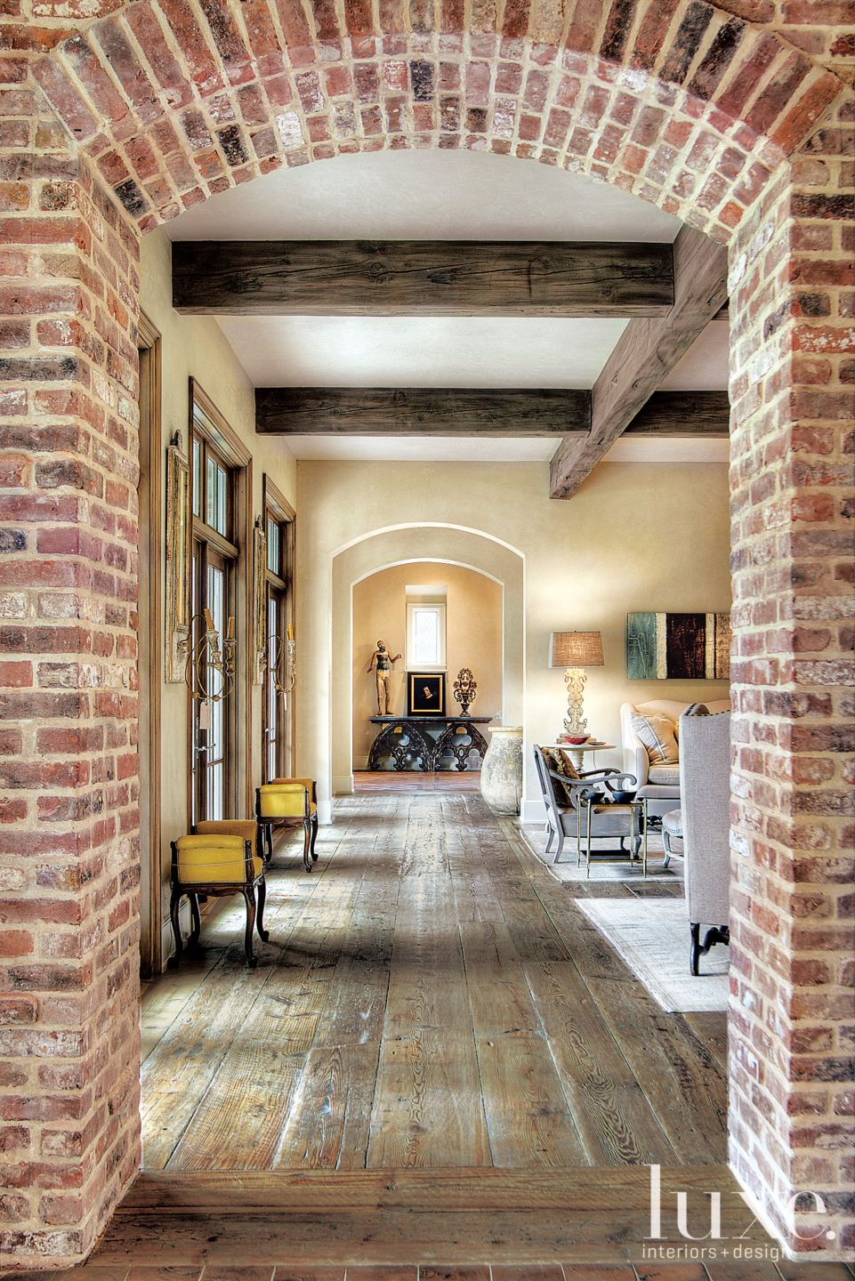 Traditional Neutral Hallway with Arched Brick Entry