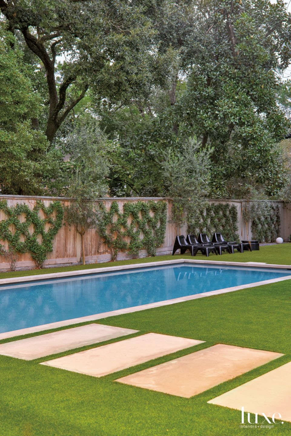 Modern Neutral Pool Area with Black Lounge Chairs